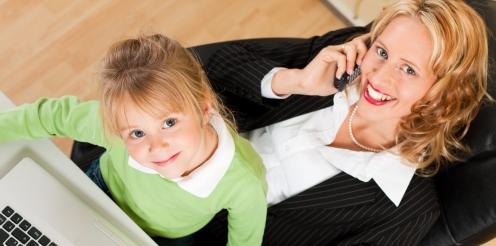 Geschäftsfrau und Mutter arbeitet mit Tochter im Arm im Internet